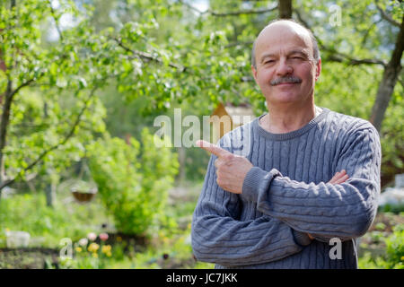 Mature man sitting in garden near apple tree in countryside. He shows index finger aside. - Stock Photo