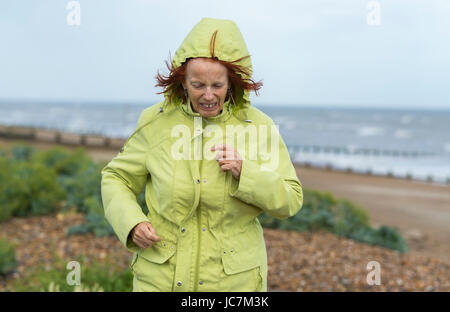 Middle aged woman running on a beach in cold weather dressed in a coat to keep warm, on a dull day in the UK. - Stock Photo