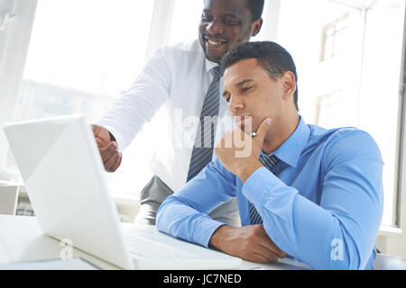 African-american businessman explaining new project to his colleague in office - Stock Photo