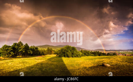 Double Rainbow over Landscape at Sunset with City of Nitra in Background - Stock Photo