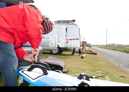 windsurfer getting equipment ready on the beach in the maharees county kerry ireland - Stock Photo