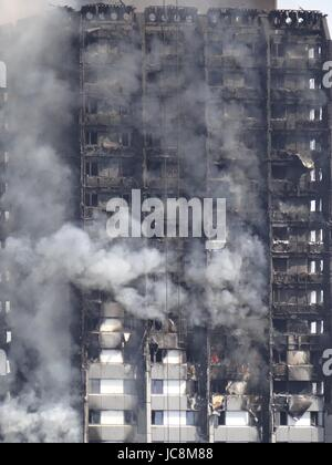 Firefighters are trying to stop he fire in West London where the Grenfell Tower was blazing over night, meanwhile - Stock Photo