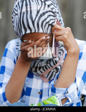 London, Britain. 14th June, 2017. A woman is awaiting news of her friend who was caught up in a fire that engulfed - Stock Photo