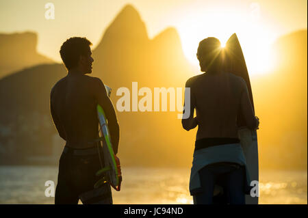 RIO DE JANEIRO - MARCH 20, 2017: Sunset silhouettes of two young surfers with surfboards at Arpoador with two brothers - Stock Photo