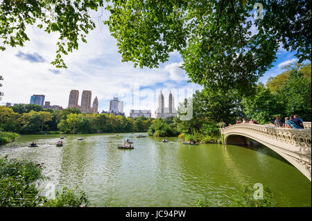 NEW YORK CITY - SEPTEMBER 3, 2016: Tourists row boats to take in the view of the famous Bow Bridge and Central Park - Stock Photo