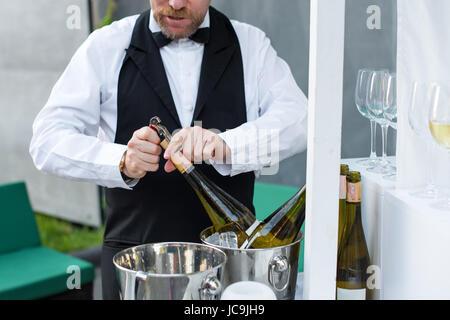 Professional waiter opening bottle of wine with corkscrew. - Stock Photo