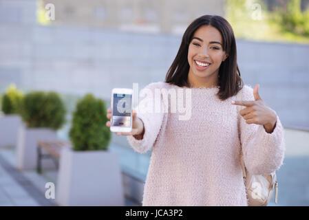 Fun cheerful woman enjoying using new app - Stock Photo