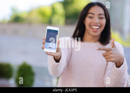 Dedicated creative woman using smartphone for showing data - Stock Photo
