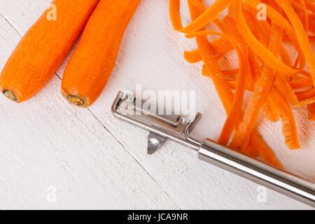 Frische orangene Karotten rüben mohrrüben geschält mit Sparschäler und Schalen auf einem weißen Holzbrett - Stock Photo