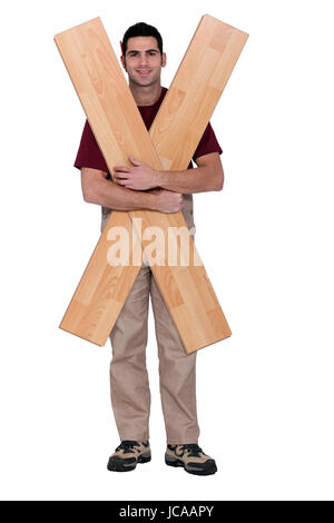 Carpenter with floorboards - Stock Photo