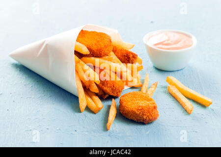 Golden fish nuggets with fried potato chips or French fries spilling out of a takeaway paper cone onto a blue surface - Stock Photo