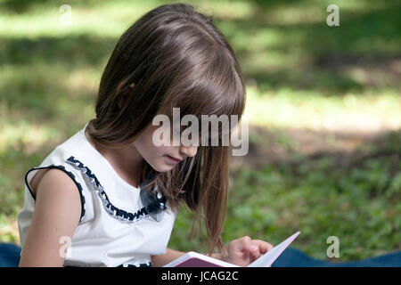 Portrait of sweet little girl in nature while reading a book - Stock Photo