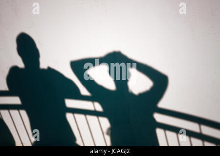 Creative photo of people shadows on white wall - Stock Photo