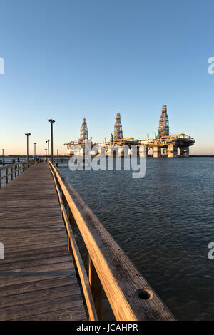Deepwater drill rigs temporarily in storage, fishing pier.