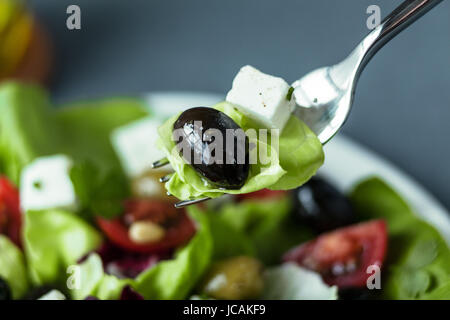 Eating a mixed Greek salad with a black olive, feta cheese and lettuce on a fork above a plate of salad with focus - Stock Photo