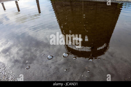 Old cooling tower and three smokestacks of the cogeneration plant reflected in water - Stock Photo