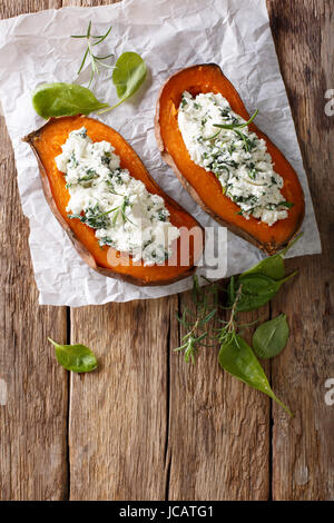 Baked sweet potato stuffed with spinach and cream cheese close-up on the table. vertical view from above - Stock Photo