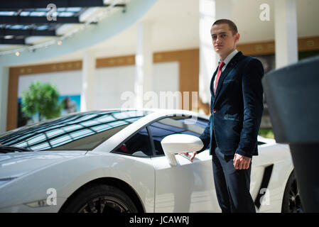 young businessman in suit standing next to a car - Stock Photo