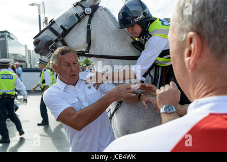 Chelsea fan held back by police officer outside the stadium at the FA Cup Final 2017 Chelsea vs Arsenal in Wembley. - Stock Photo
