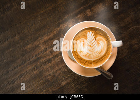 Close focus on cup of hot cappuccino coffee with latte art on dark brown wood table. - Stock Photo