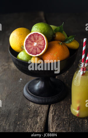 Bowl of assorted fresh citrus fruit with a halved blood orange with its distinctive red pulp in the foreground with - Stock Photo