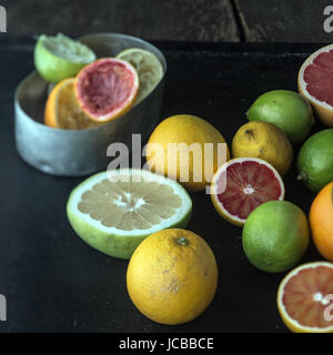 Juicing a selection of fresh citrus fruit with grapefruit, oranges, limes and lemons and a metal container with - Stock Photo