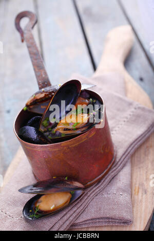 Serving of delicious gourmet freshly steamed marine mussels in a copper pot with an open one displayed below on - Stock Photo