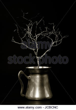 Wire sculpture tree planted inside a brass pitcher against a black background. - Stock Photo