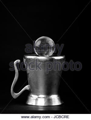 A brass pitcher turned upside down with a glass sphere sitting atop of it against a black background - Stock Photo