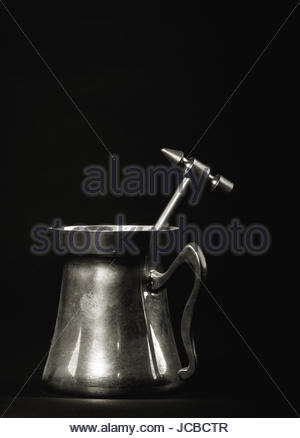 Brass pitcher with a brass hammer inside it against a black background - Stock Photo