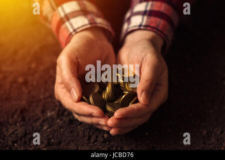 Farmer with handful of coins over soil land, making money and gaining profit in agriculture - Stock Photo