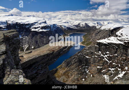 Hiker enjoying the view from Trolltunga in Norway after a long trek - Stock Photo