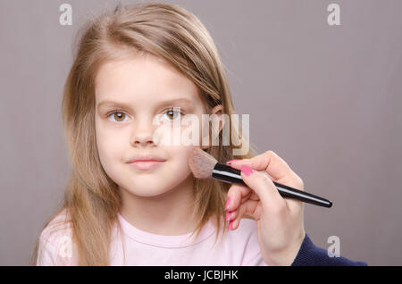 Makeup artist deals powder brush on the face of a five year old girl - Stock Photo