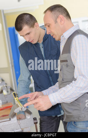 two carpenters measuring a piece of material - Stock Photo