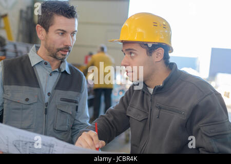 male worker showing something to co-worker at his notebook papers - Stock Photo