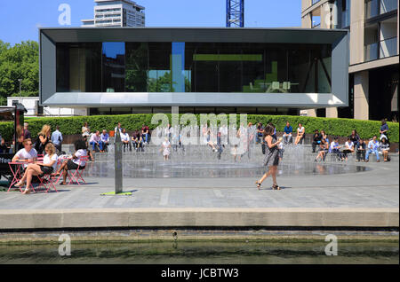 People relaxing by the fountains in Paddington Basin, west London, UK - Stock Photo