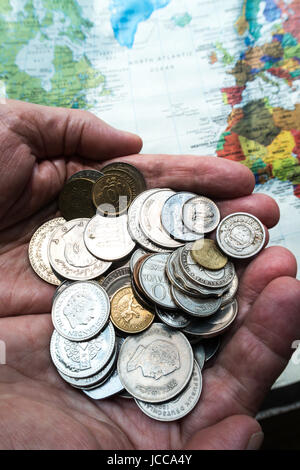 Hands Holding Multiple International Coins - Stock Photo