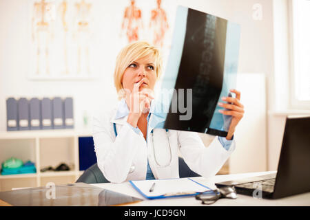 Female doctor studying spine x-ray - Stock Photo