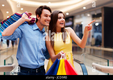 Woman showing something in the shopping mall - Stock Photo