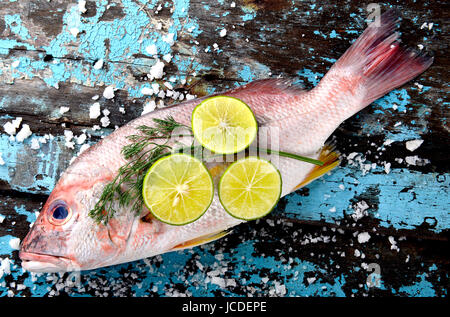 Fresh red snapper fish from fishery market with salt and lemon set on wooden plate. - Stock Photo