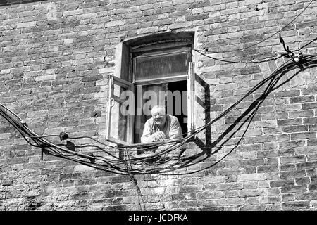 VALAAM, RUSSIA - Aug 15 2015, View of an old man looking out from a window of a brick building, on Aug 15 2015 in - Stock Photo