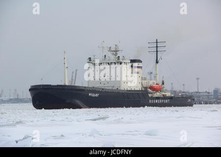 Russian diesel-electric icebreaker 'Mudyug' at the entrance to the port city. It breaks through the ice (clears - Stock Photo