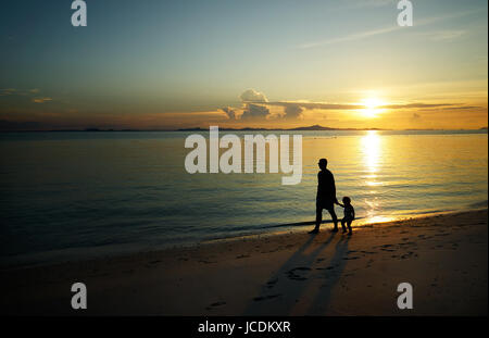 Father and his child walking on sunset beach , silhouette shot . - Stock Photo