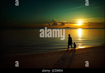 Father and his child walking on sunset beach , silhouette shot and tone image . - Stock Photo