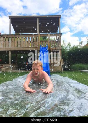 Children playing on a waterslide in the garden during summertime - Stock Photo