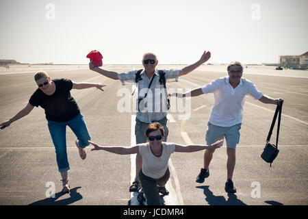 Funny group of tourist people imitating airplane at the airport runway. - Stock Photo