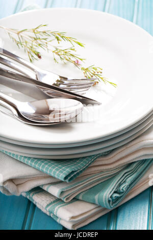 A stack of clean white plates with silverware on blue napkins - Stock Photo