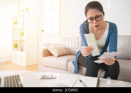 beautiful girl stressed over bills. surprised young woman using computer and holding bill and bank statements sitting - Stock Photo