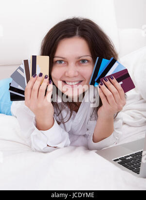 Woman with a fistful of credit cards lying on her bed with her laptop browsing online for something to purchase - Stock Photo