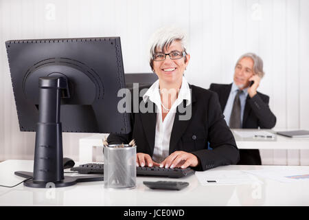 Smiling secretary or personal assistant sitting working at her desk with her boss visible on the telephone in the - Stock Photo